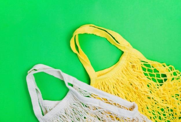 Het concept van nul afval zonder plastic. katoenen herbruikbare mesh boodschappentas op een groene achtergrond.