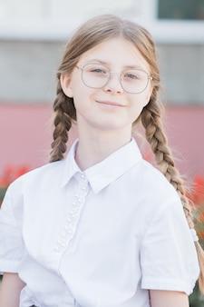 Het concept van onderwijs. lachende meisje leerling van de basisschool in glazen in uniform en staartjes. portretmeisje in glazen klaar voor school.
