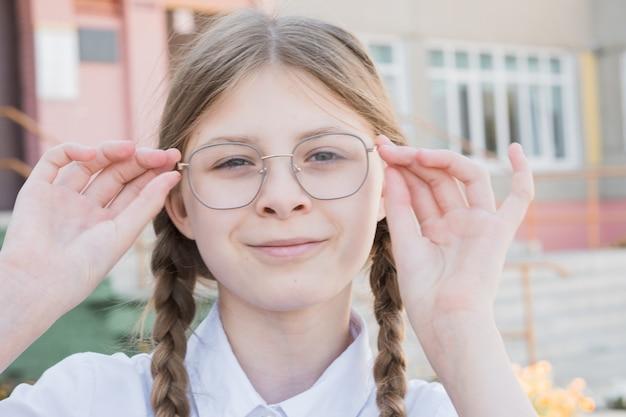 Het concept van onderwijs. lachende meisje leerling van de basisschool in glazen in uniform en staartjes. schoolmeisje past zijn bril klaar voor school. portret slimme student