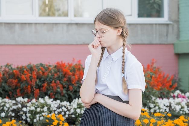 Het concept van onderwijs. meisje leerling van de basisschool in glazen in uniform. nadenkend meisje in glazen klaar voor school.