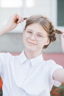 Het concept van onderwijs. meisjesleerling van de basisschool met een bril in uniform die voor de gek houdt met staartjes en een glimlach. grappig meisje in glazen klaar voor school.