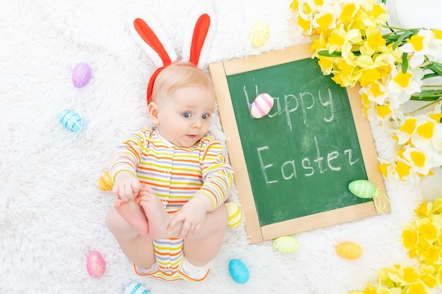 Het concept van pasen, een baby in een konijnenhoed op een bed met paaseieren en de inscriptie vrolijk pasen