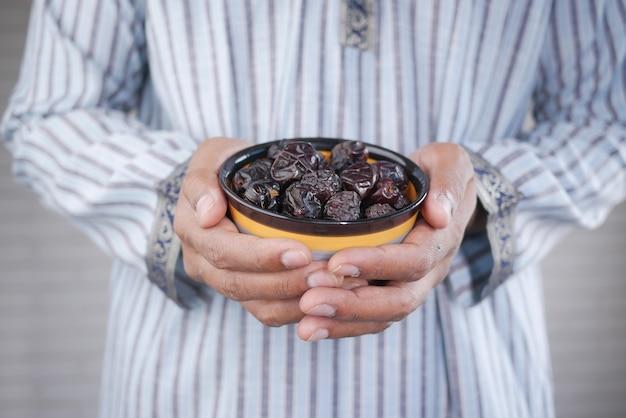Het concept van ramadan hand met een kom met dadelvruchten