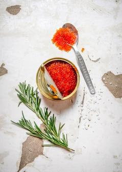 Het concept van rode kaviaar. rode kaviaar met rozemarijn. op rustieke achtergrond. bovenaanzicht