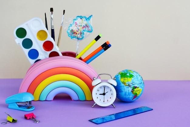 Het concept van terug naar school, diversiteit en inclusiviteit. etui in de vorm van een heldere regenboog met een lolly in de vorm van een eenhoorn, verf, penselen, potloden, wekker, nietmachine, liniaal en planeet
