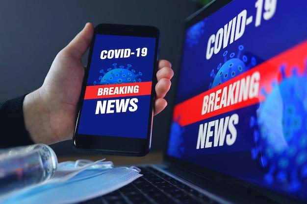 Het concept van thuisblijven is de epidemie van het coronavirus covid-19. antiseptisch gezichtsmasker en telefoon. laptop scherm covid-19 breaking news achtergrond.