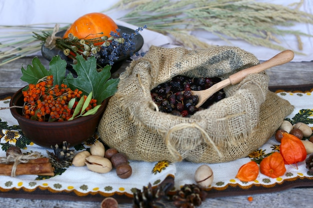 Het concept van traditionele geneeskunde met gedroogde rozenbottel bessen in een zak op een houten tafel