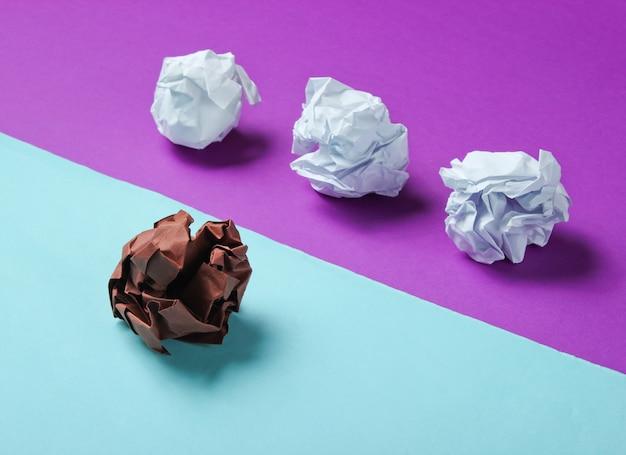 Het concept van uniciteit, rassendiscriminatie. witte en bruine verfrommeld papier ballen op paars blauwe tafel. minimalisme
