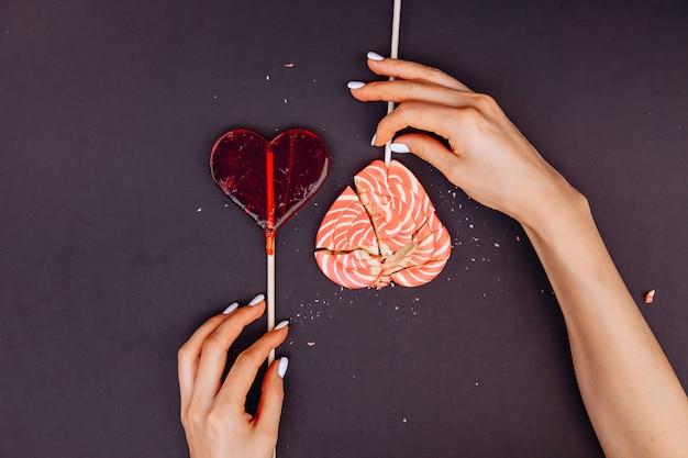 Het concept van valentijnsdag. de handen van vrouwen die een gebroken hart bij elkaar houden. karamel gebroken hart.