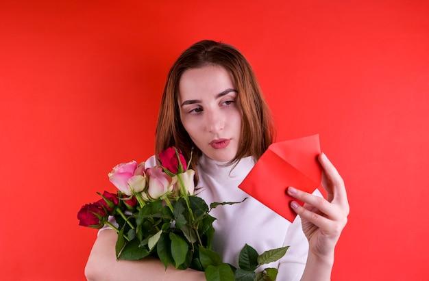 Het concept van valentijnsdag en vrouwendag. gelukkig jong meisje dat een boeket van rozen houdt