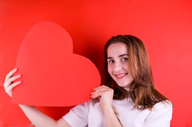 Het concept van valentijnsdag of vrouwendag. jong meisje met een groot rood hart in haar handen. kopieer ruimte. fotolijst.