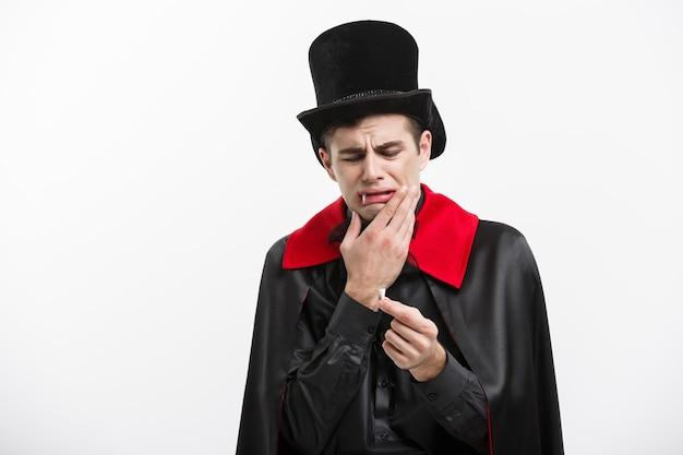 Het concept van vampierhalloween - het portret van knappe kaukasische vampier die pijn doet verliest zijn vampiertand.
