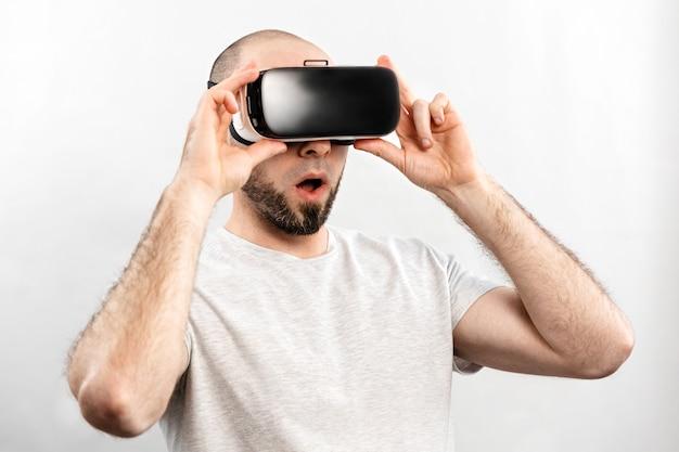 Het concept van virtuele realiteit. portret van een verraste volwassen man in virtual reality-bril, met zijn mond een beetje open. witte achtergrond.