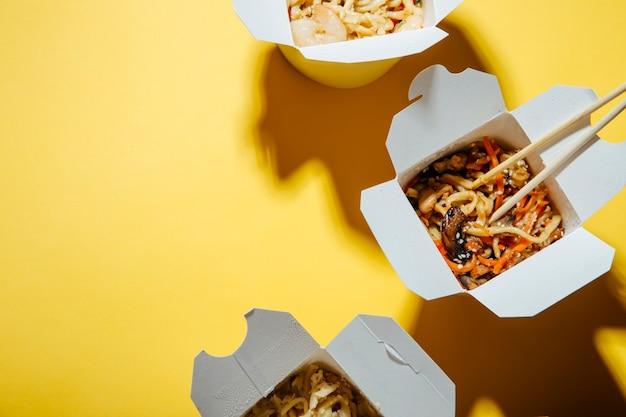 Het concept van voedselbezorging op een gele achtergrond noedels in dozen