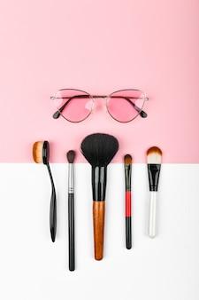 Het concept van vrouwelijke cosmetica. vrouwelijke geïmproviseerde middelen. set van kleurrijke cosmetica op een roze. plat lag.