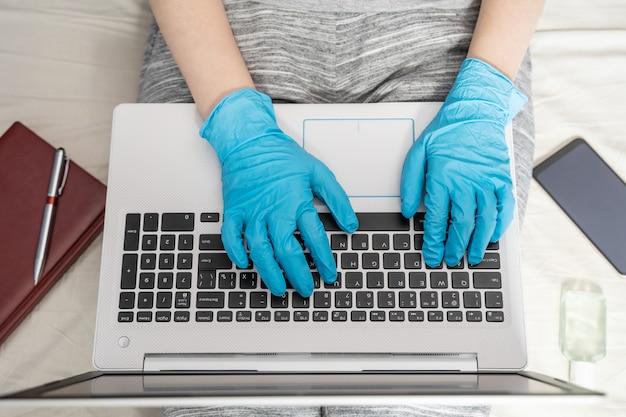 Het concept van werken op afstand tijdens een epidemie. een vrouw in wegwerphandschoenen werkt op een laptop. bovenaanzicht van de werkplek
