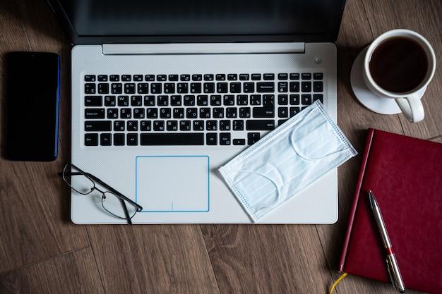 Het concept van werken op afstand tijdens een epidemie. laptop op de tafel, hygiëneproducten