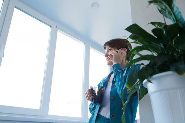 Het concept van werkgelegenheid, interviews, reclame voor digitale technologie - vrouw die koffie drinkt en aan de telefoon spreekt. de glimlachende vrouw met kop belt. ochtend van meisje