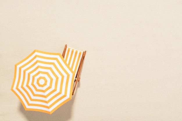 Het concept van zomervakantie. bovenaanzicht op een ligstoel onder een parasol op het zandstrand