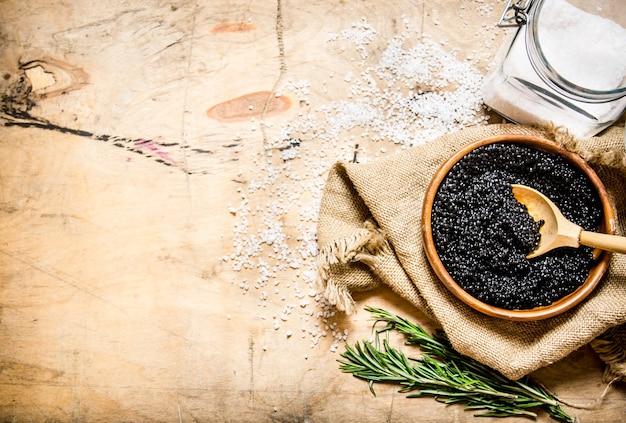 Het concept van zwarte kaviaar zwarte kaviaar in een kopje met zout en rozemarijn op een houten tafel