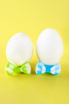 Het concept voor de internationale vriendschapsdag. eieren in bogen op gele pastel.