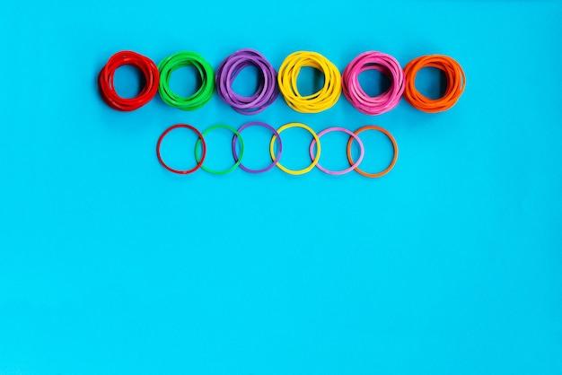 Het conceptengroep van het groepswerk kleurrijk elastiekje op blauwe achtergrond met exemplaarruimte