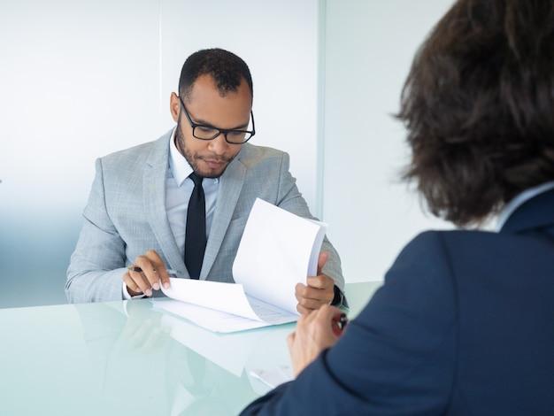 Het contract van de zakenmanlezing tijdens vergadering