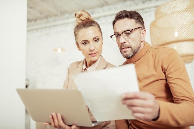 Het controleren van schetsen. twee gemotiveerde ontwerpers kijken aandachtig naar hun schetsen voor nieuwe collectie met laptop en vel papier.
