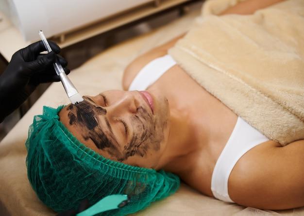 Het cosmetische masker van zwarte houtskool op het gezicht van de patiënt borstelen
