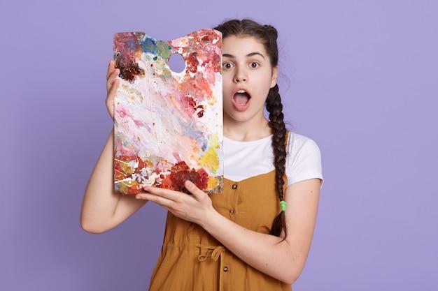 Het creatieve jonge jonge vrouw schilderen in haar studio