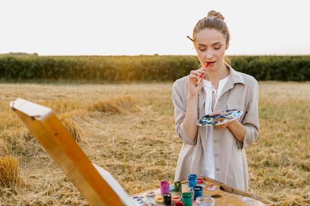 Het creatieve jonge vrouwenhand schilderen in de aard