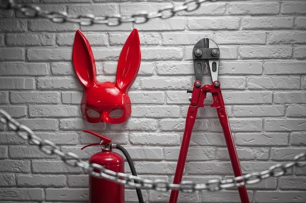 Het creatieve ontwerp van een vuurstenen muur met een konijnenmasker, brandblussers en boutensnijder met een uitgerekte ketting