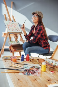 Het creatieve peinzende schildersmeisje schildert een kleurrijk beeld op canvas met olieverf in workshop.