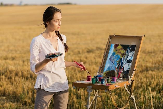 Het creatieve vrouwenhand schilderen in de aard