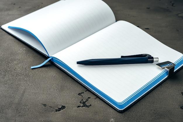 Het dagboek en de pen van mensen op donkergrijze achtergrond