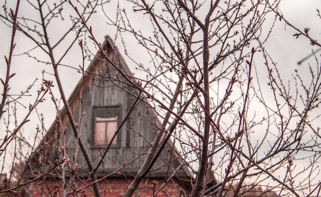 Het dak en de zolder van een landhuis door de takken van bomen in het vroege voorjaar.
