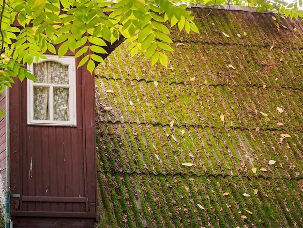 Het dak van een oude huisclose-up het dak is bedekt met groen mos