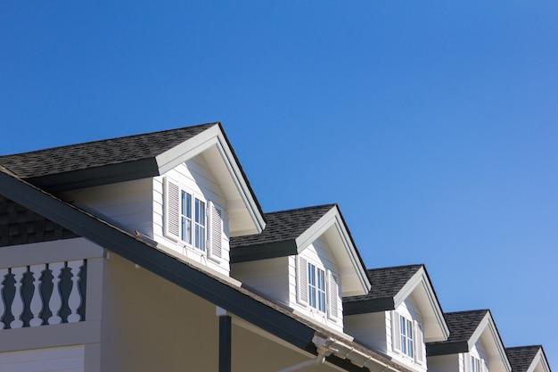 Het dak van het huis met mooi venster op de blauwe hemelachtergrond.