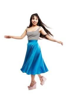 Het dansende jonge meisje. glimlachende brunette met lang haar in een lange blauwe rok. geïsoleerd op witte ruimte. verticaal.