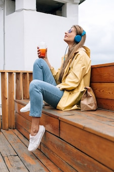 Het de herfstportret van modieuze gelukkige vrouw het luisteren muziek en klaar om haar te hebben haalt lunch weg