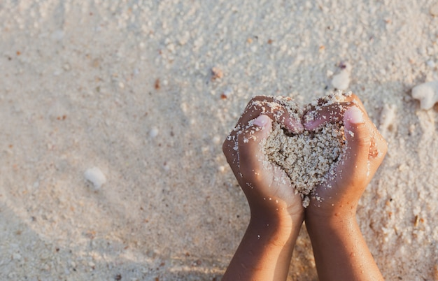 Het de holdingszand van het kindmeisje maakt hartvorm in handen en speelt op het strand in de zomervakantie