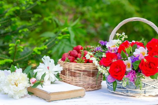 Het de zomerstilleven van de lente met een boeket van bloemen in een mand