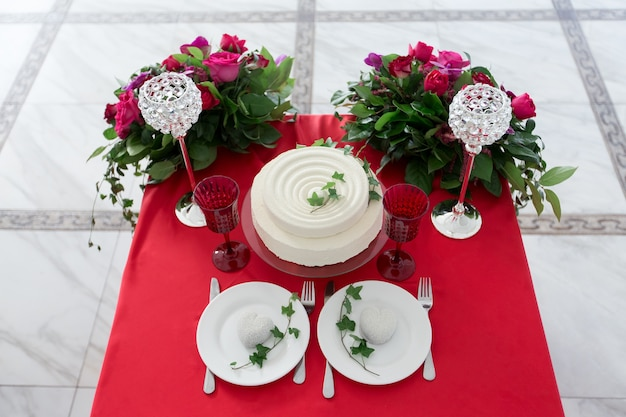 Het decor van de bruiloft - trouwtafel voor twee. witte cake, bloemen, kristallen glazen op de rode tafel. uitzicht van boven.