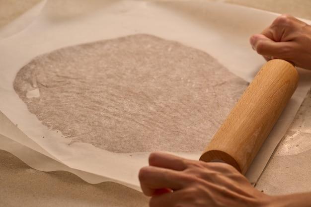 Het deeg kneden met deegroller voor de bereiding van de peperkoekman
