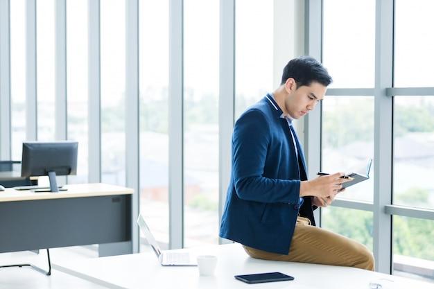 Het denken aan het aziatische jonge zakenman werken met las de nota die in het businessplan wordt geregistreerd