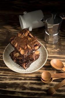 Het dessert van browniechocolade macadamia gebakken snoepje op houten achtergrond