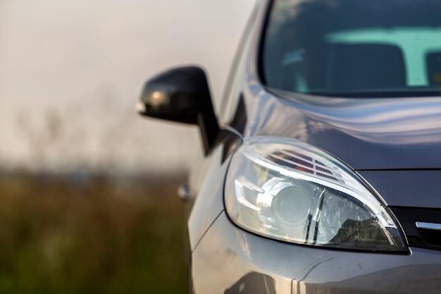 Het detaildeel van de close-up van zwarte glanzende auto-koplamp, spiegel, motorkap en radiatorrooster op vage openluchtachtergrond. vervoer, prestige, modern ontwerpconcept.