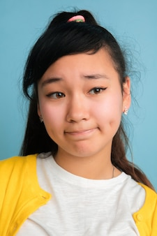 Het dichte omhooggaande portret van de aziatische tiener dat op blauwe studioachtergrond wordt geïsoleerd. mooi vrouwelijk donkerbruin model met lang haar. concept van menselijke emoties, gezichtsuitdrukking, verkoop, advertentie. ziet er verdrietig uit.