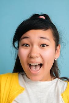 Het dichte omhooggaande portret van de aziatische tiener dat op blauwe studioachtergrond wordt geïsoleerd