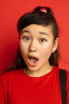 Het dichte omhooggaande portret van de aziatische tiener dat op rode studioachtergrond wordt geïsoleerd